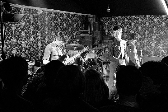 UNITED KINGDOM - MARCH 14:  Photo of JOY DIVISION; Bernard Sumner, Ian Curtis, Peter Hook performing live onstage at Bowdon Vale Youth Club  (Photo by Martin O'Neill/Redferns)