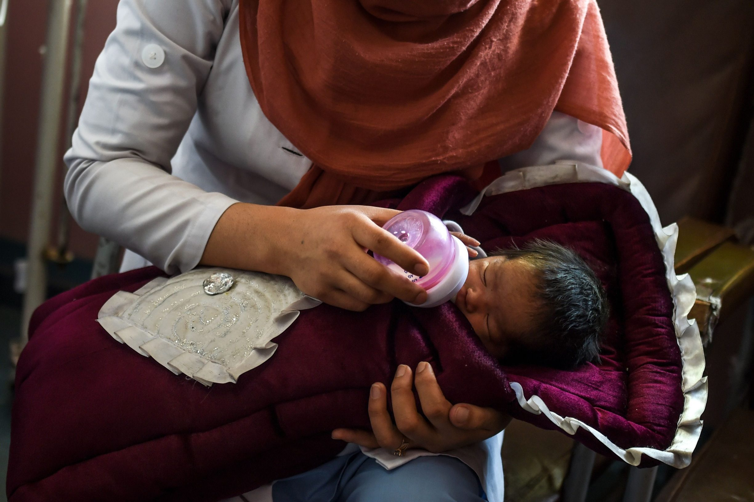A nurse feeds a newborn baby rescued and brought to Ataturk Children hospital, after the mother was killed during a gunmen attack on a maternity hospital, in Kabul on May 15, 2020. - Gunmen who stormed a hospital in the Afghan capital this week had come to