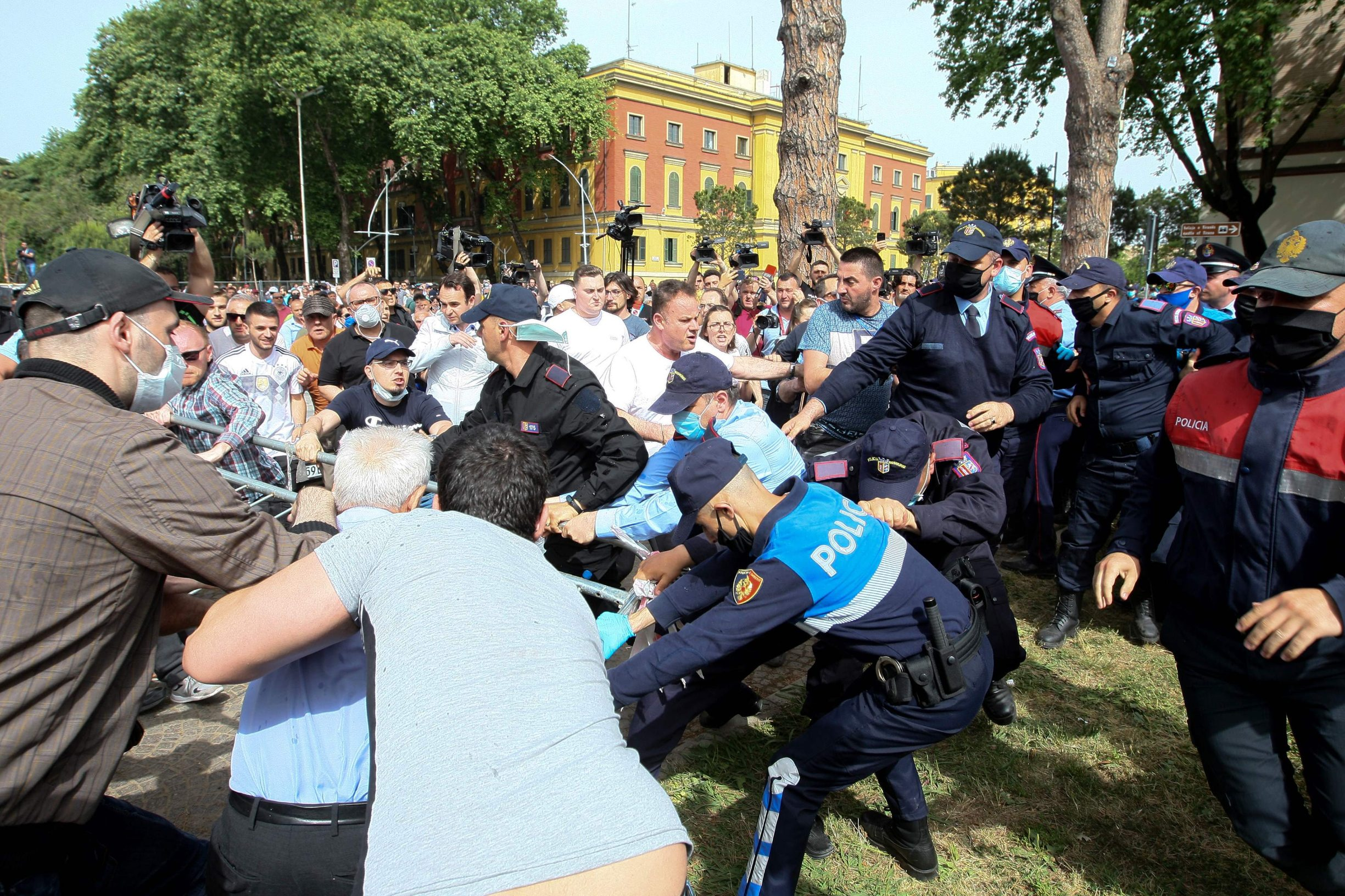 Albanian protestors clash with police forces in a desperate attempt to prevent the demolition of the 70-year old neoclassical building of the National Theatre, on May 17, 2020. - Albanian police Sunday clashed with protesters including opposition supporters angry over the demolition of the national theatre, leading officers to detain nearly 40 people. (Photo by Gent SHKULLAKU / AFP)