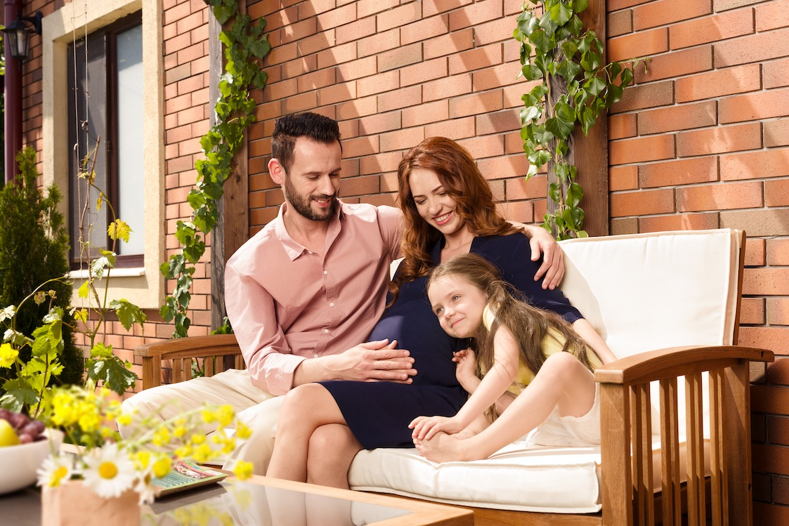 Young family with expecting mother sitting on garden bench in front of brick-lined façade