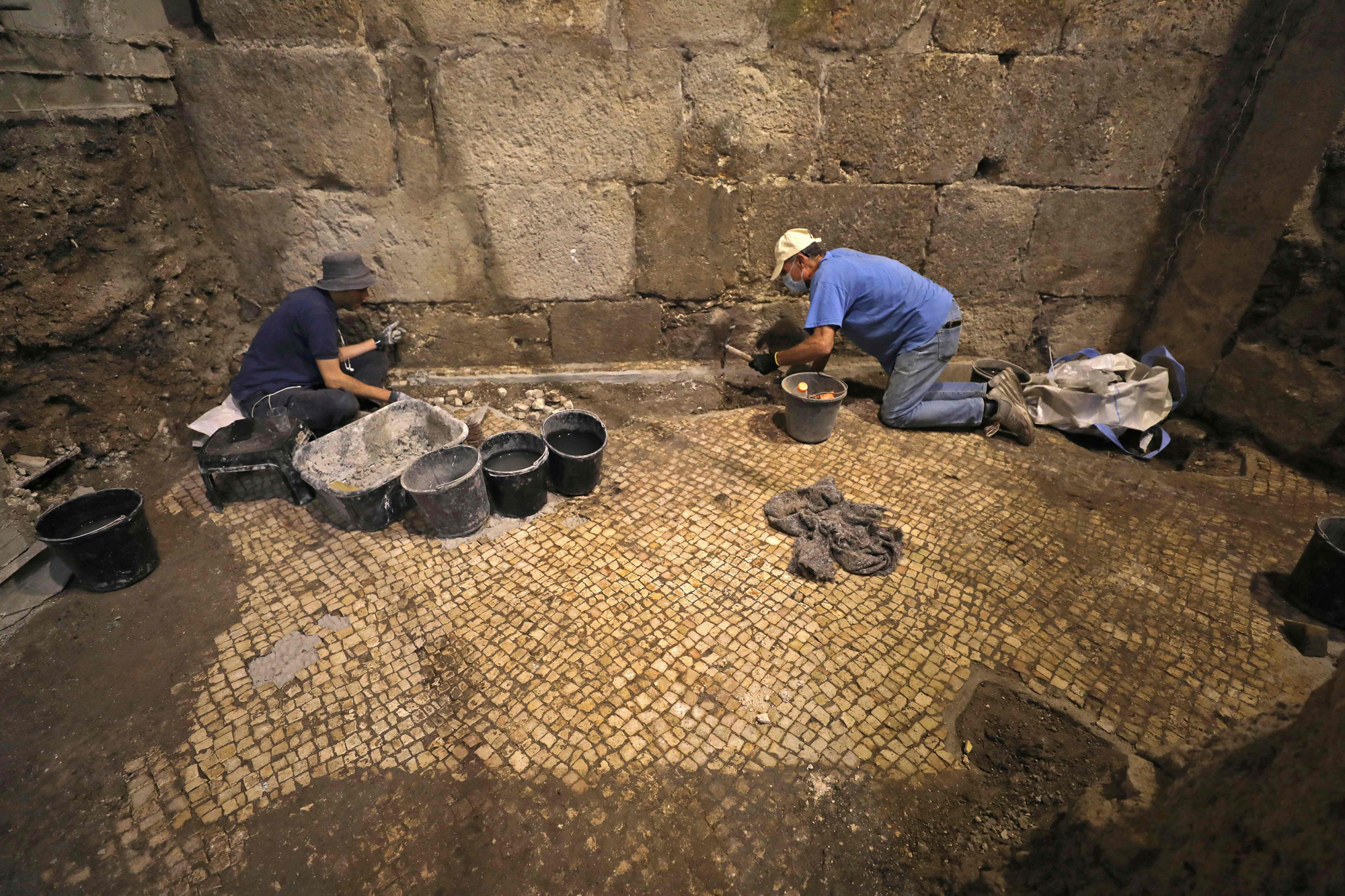 Archaeologists of the Israel Antiquities Authority work at an excavation at a subterranean system hewn in the bedrock beneath a 1400-year-old building near the Western Wall in Jerusalem's Old City, on May 19, 2020. (Photo by MENAHEM KAHANA / AFP)