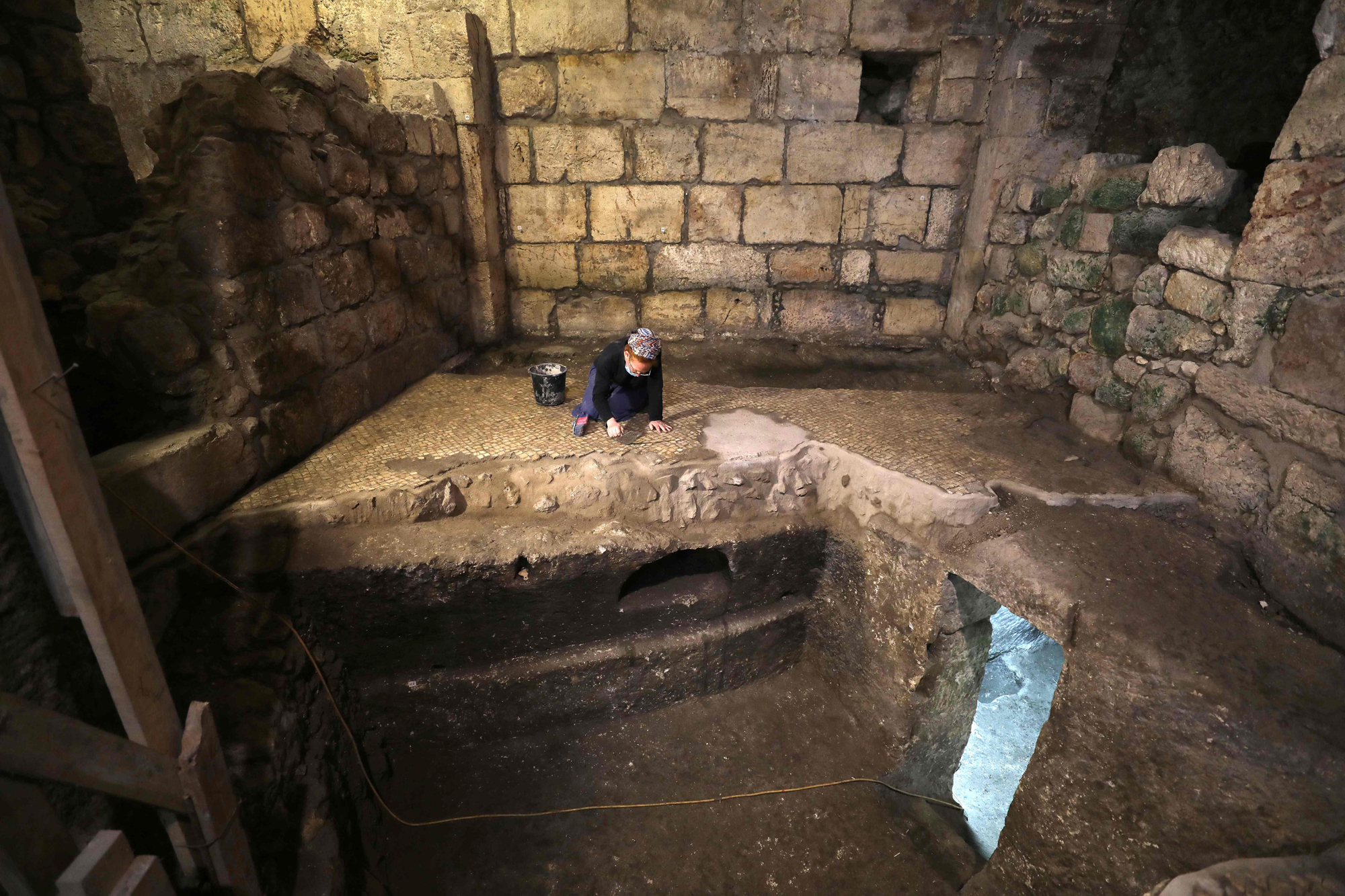 Tehila Sadiel, an archaeologist of the Israel Antiquities Authority, works at an excavation at a subterranean system hewn in the bedrock beneath a 1400-year-old building near the Western Wall in Jerusalem's Old City, on May 19, 2020. (Photo by MENAHEM KAHANA / AFP)