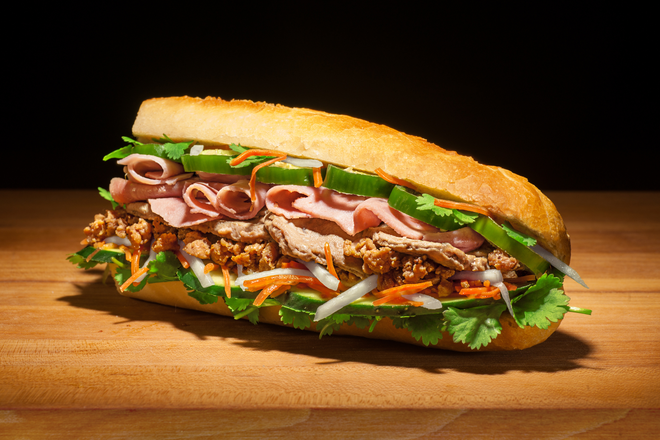 Aspirational style shot of a huge Bánh mì sandwich with cilantro, jalepenos, pickled carrots and daikon, Vietnamese ham, chopped pork and pork steak, and cucumbers, on fresh baguette.