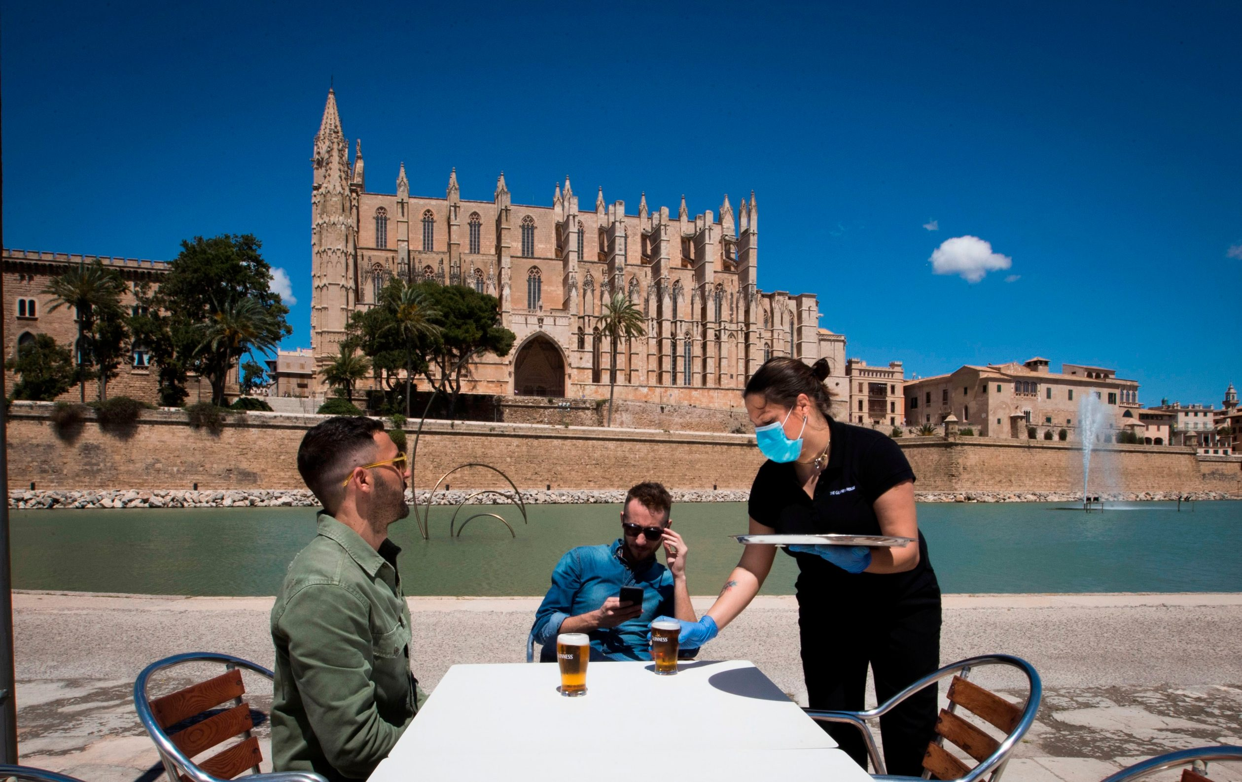 A waitress wearing a face mask and gloves serves customers at a terrace bar near the Cathedral in Palma de Mallorca on May 11, 2020, as Spain moved towards easing its strict lockdown in certain regions. - Spaniards returned to outdoor terraces at cafes and bars as around half of the country moved to the next phase of a gradual exit from one of Europe's strictest lockdowns (Photo by JAIME REINA / AFP)