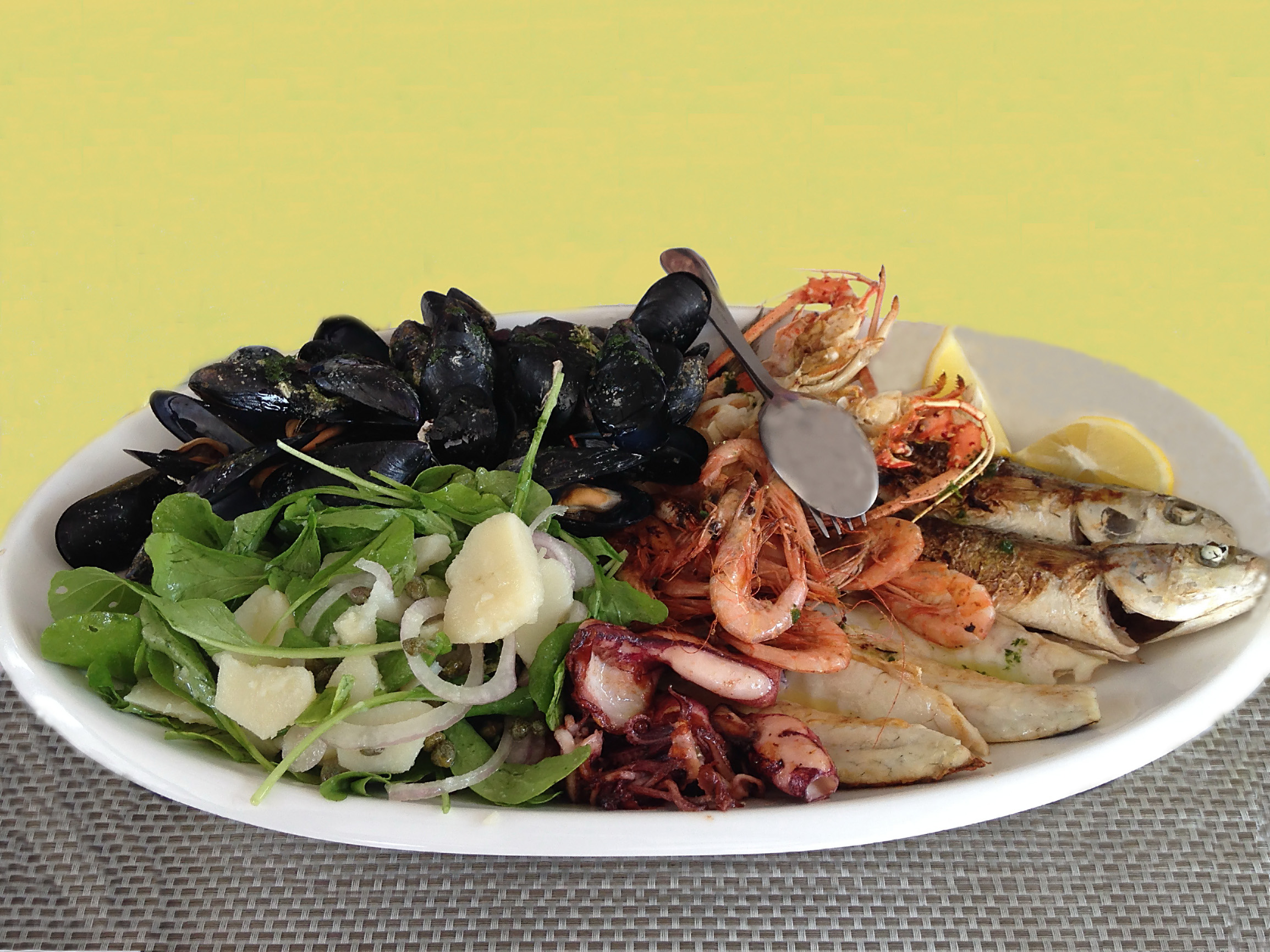 Isolated Seafood Platter: Fresh mixed grilled mussels, langoustines, shrimps, fish decorated with arugula, onion, lemon and sauce on a white plate.