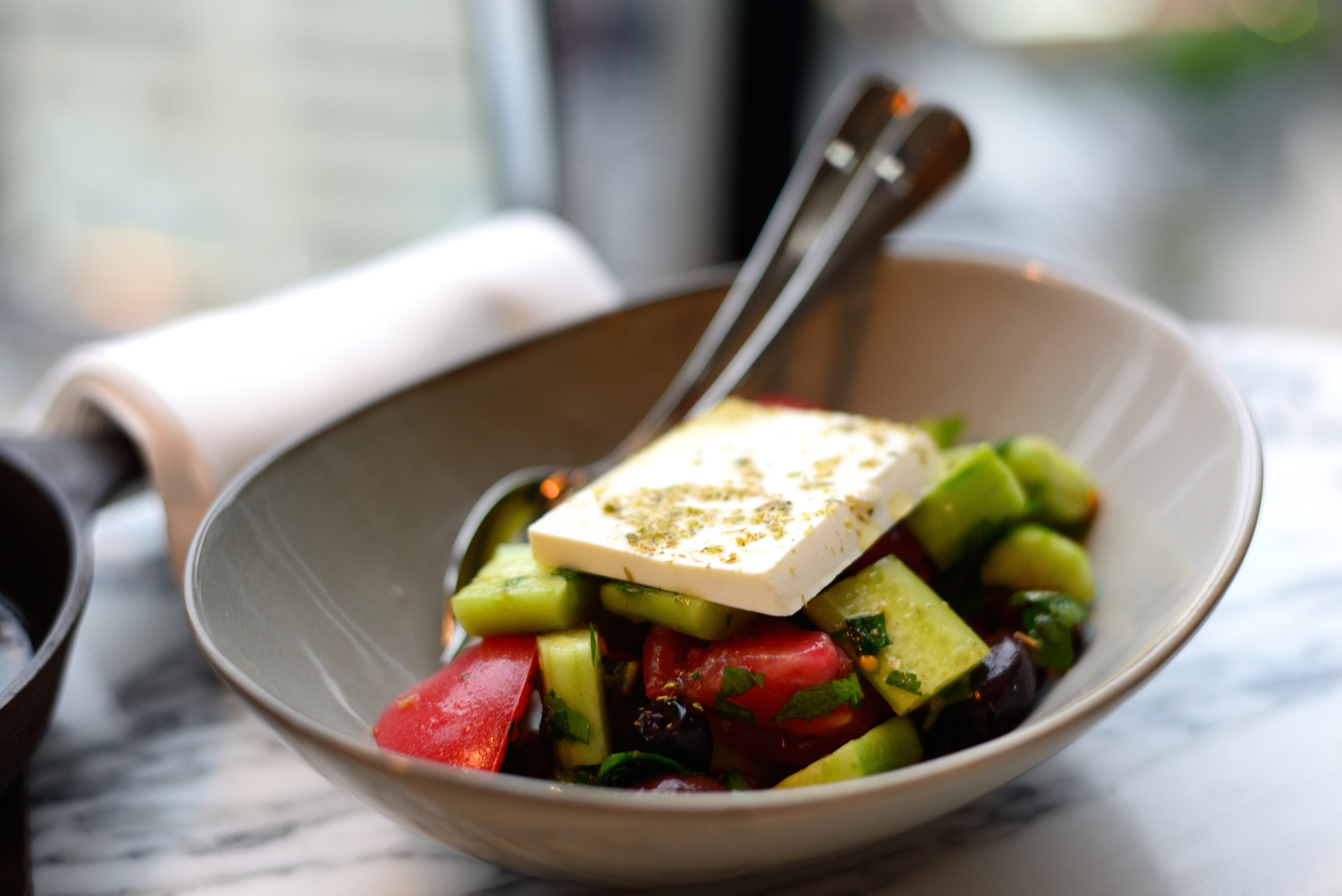 A bowl of Greek salad with a large chunk of feta cheese on top.