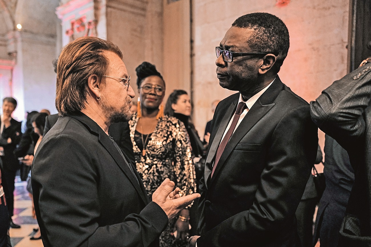 Senegalese singer Youssou N'dour (R) speaks with Irish rock band U2 singer Bono (L) as they arrive at Lyon's city hall, central eastern France, on October 9, 2019, during the funding conference of Global Fund to Fight AIDS, Tuberculosis and Malaria. The Global Fund to Fight AIDS, Tuberculosis and Malaria on October 9, 2019, opened a drive to raise  billion to fight a global epidemics but face an uphill battle in the face of donor fatigue. The fund has asked for  billion, an amount it says would help save 16 million lives, avert