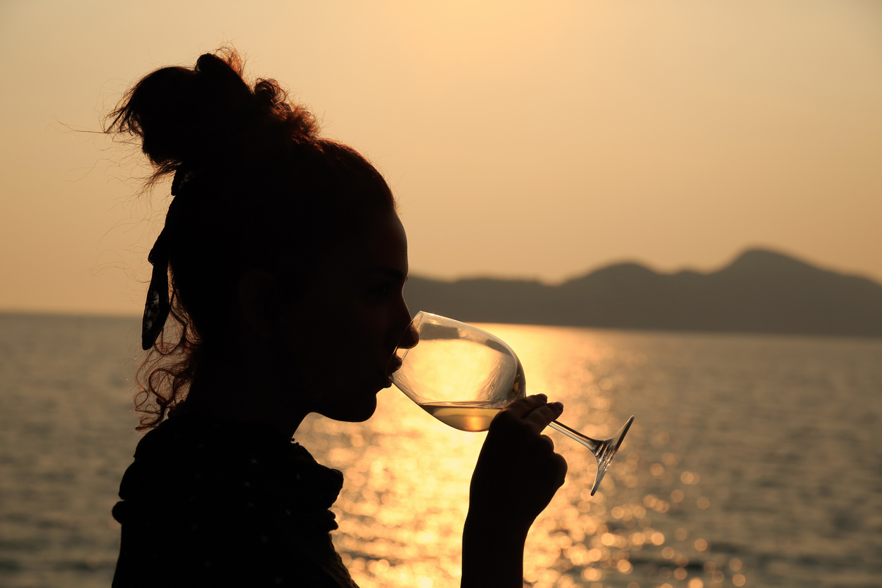 Beautiful woman drinking a glass of white wine,  at sunset.