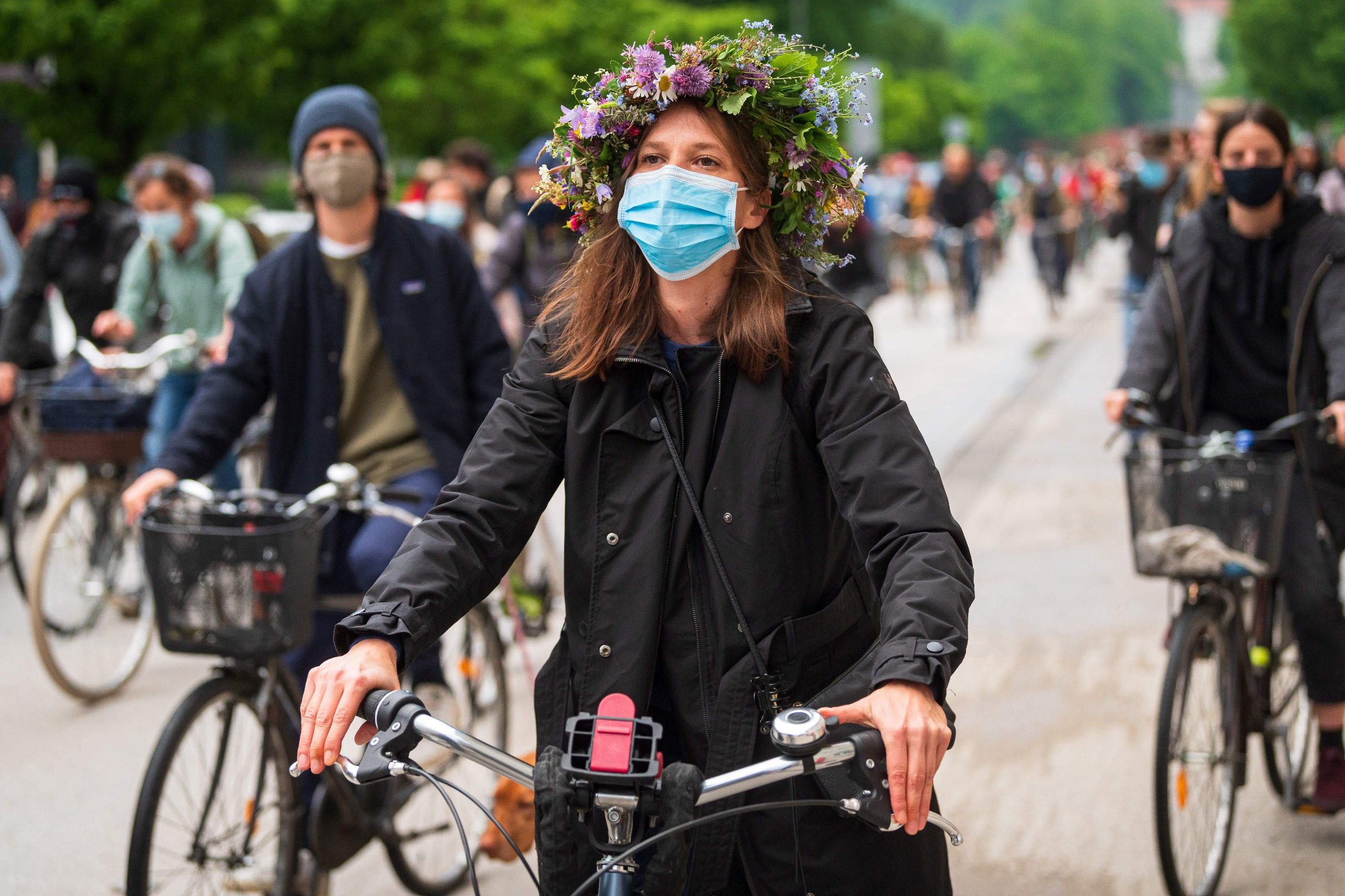 A Slovenian citizen, wearing a protective facemask, rides her bikes, on May 15, 2020, as she takes part in a demonstration to block the centre of the capital Ljubljana, to protest against the centre-right government, accusing it of corruption and of using the COVID-19 (the novel coronavirus) crisis to restrict freedom. (Photo by Jure Makovec / AFP)