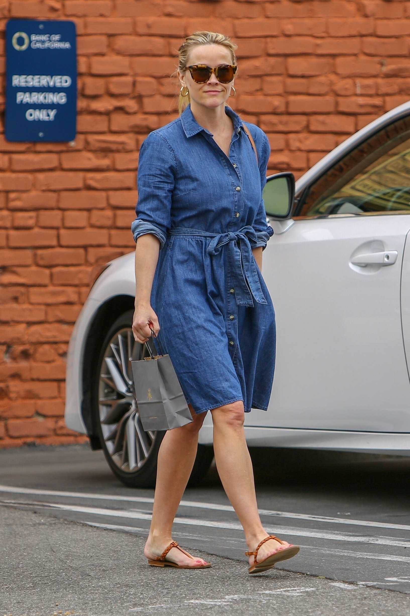 Santa Monica, CA  - *EXCLUSIVE* Reese Witherspoon looks refreshed after a three hour Sunday morning spa session at Queen Bee Salon & Spa in Santa Monica. Reese dons a denim dress and leather sandals for her solo trip to the spa. A noticeable blemish on Reese's cheek can be seen as she returns to her car with a smile.  Pictured: Reese Witherspoon    *UK Clients - Pictures Containing Children Please Pixelate Face Prior To Publication*, Image: 429478508, License: Rights-managed, Restrictions: , Model Release: no, Credit line: BACKGRID / Backgrid USA / Profimedia