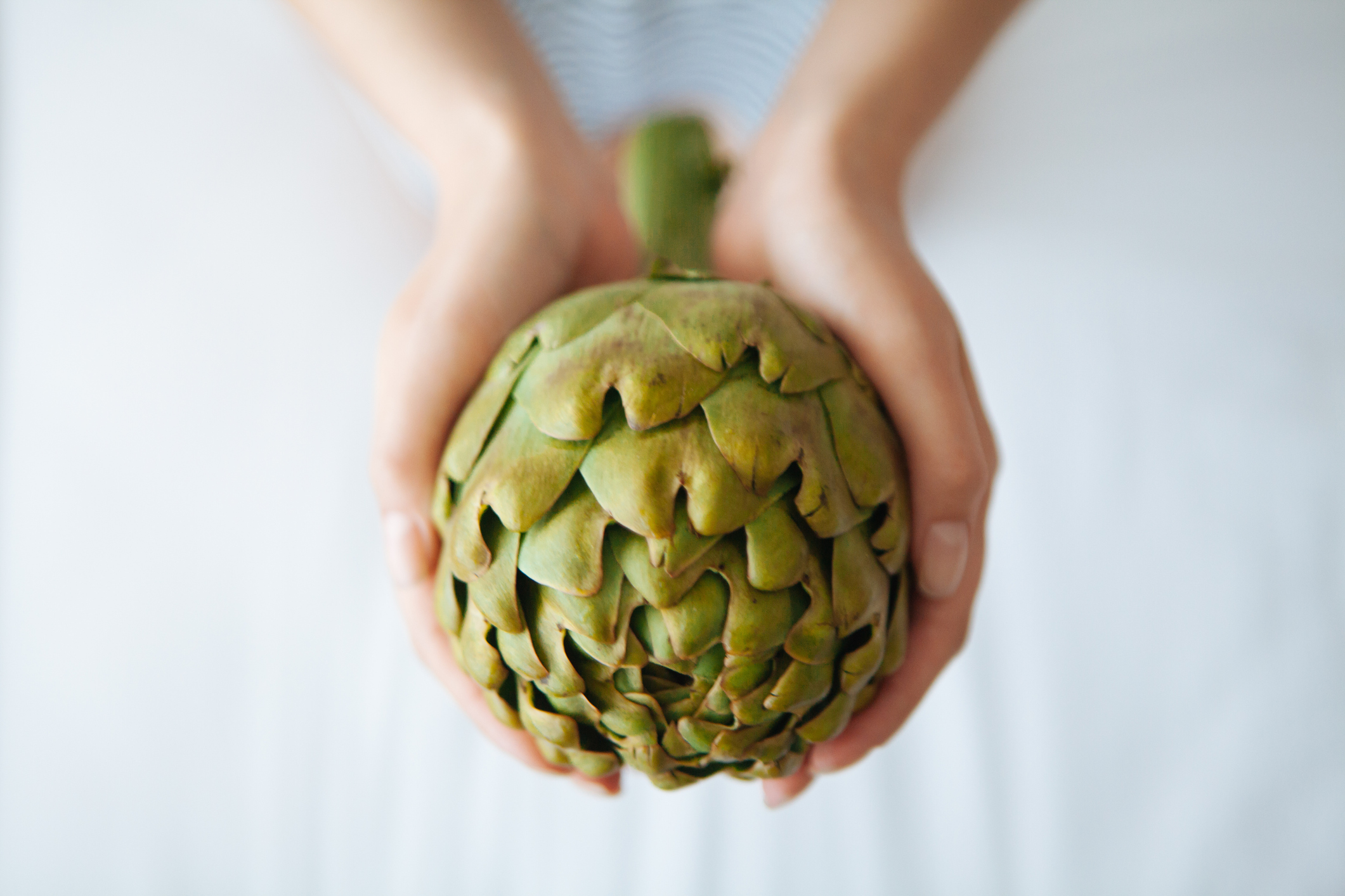 a young woman holding an artichoke in her hands