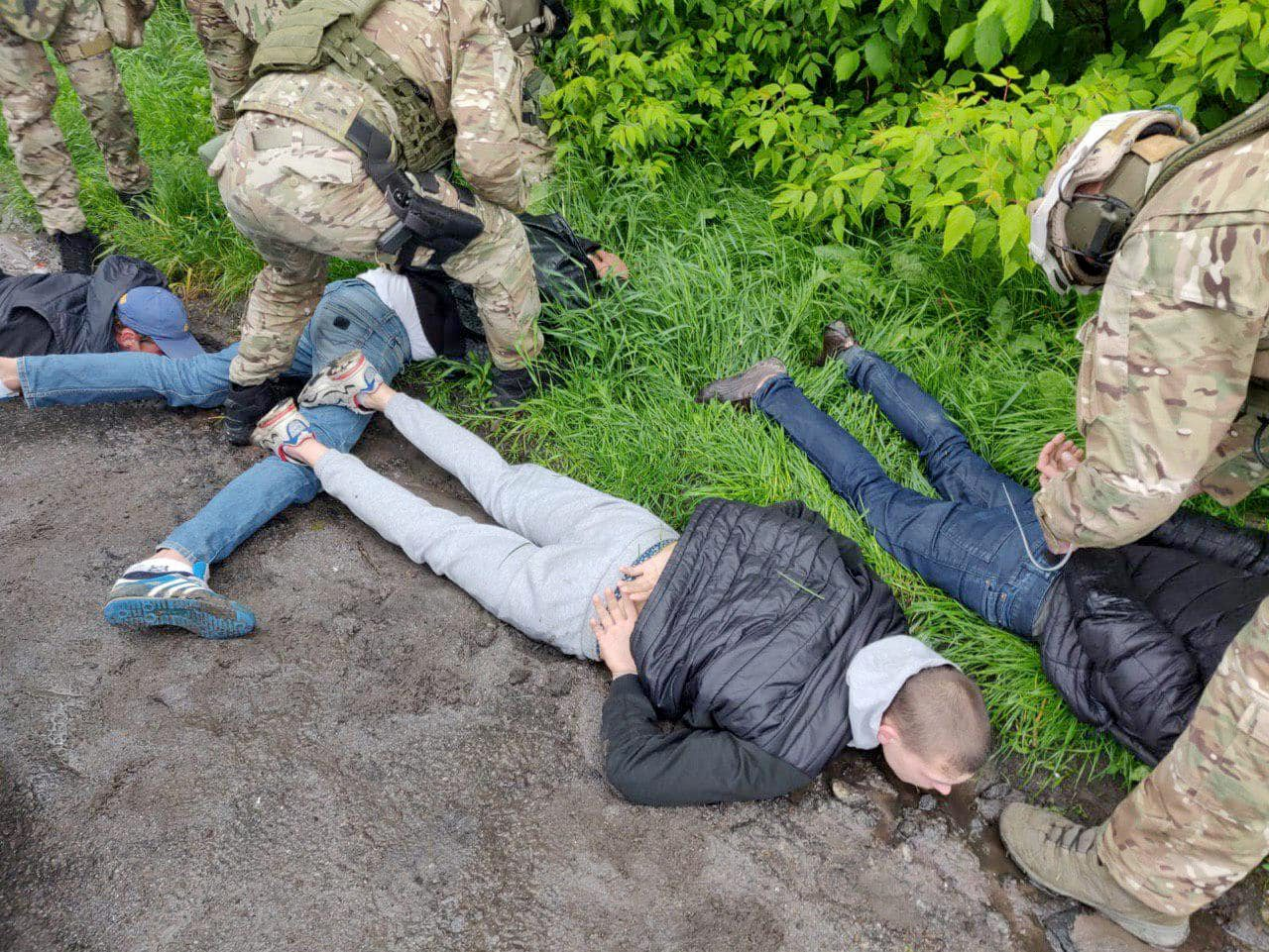 This handout picture taken and released by Ukrainian Interior Ministry press-service on May 29, 2020, shows people detained by the police in small town of Brovary, near Kiev. - Three people have been wounded and eleven arrested after a mass shootout between criminal gangs in a small town near Kiev, authorities said on May 29, 2020. Dozens of people staged a shootout early on May 29, in the streets of Brovary, a small town ten kilometres (eight miles) east of Kiev, police said. The cause of the clash was
