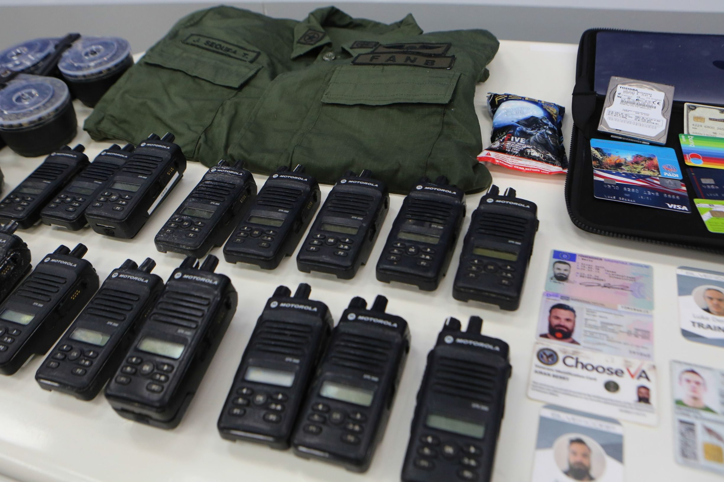 Handout picture released by the Venezuelan Presidency showing identification cards, two-way radios and other military gear allegedly seized to US citizens arrested by security forces during a meeting with members of the Bolivarian National Armed Forces (FANB), at Miraflores Presidential Palace in Caracas on May 4, 2020. - Venezuela is to try two Americans, identified as Luke Denman and Airan Berry, allegedly captured during a failed sea attack by mercenaries, President Nicolas Maduro said on May 6. (Photo by Marcelo Garcia / Venezuelan Presidency / AFP) / RESTRICTED TO EDITORIAL USE - MANDATORY CREDIT