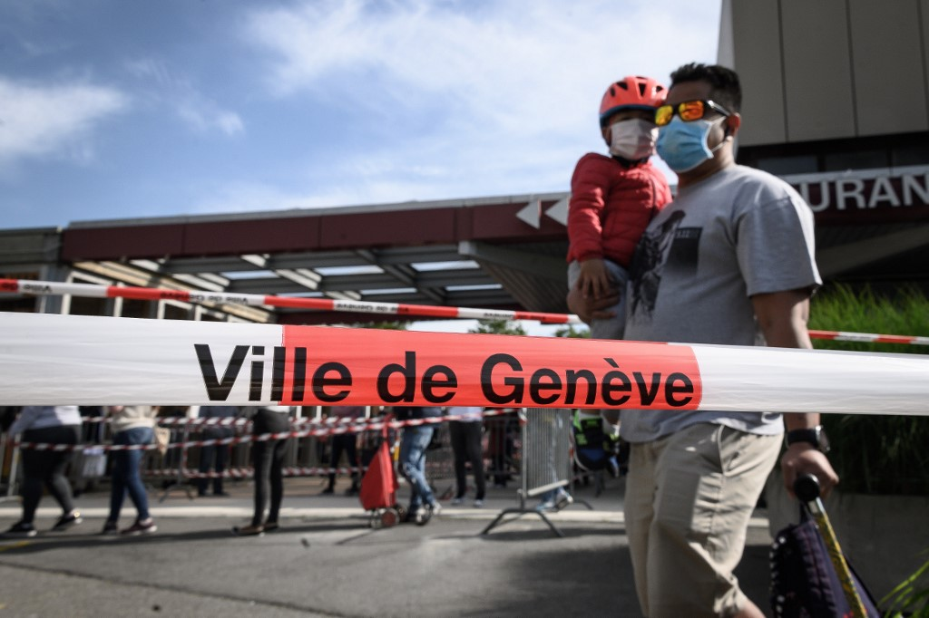 A father and his son wearing protective face masks queue behind warning police tape at a free food distribution on May 9, 2020 in Geneva as the COVID-19 pandemic casts a spotlight on the usually invisible poor people of Geneva, one of the world's most expensive cities. (Photo by Fabrice COFFRINI / AFP)