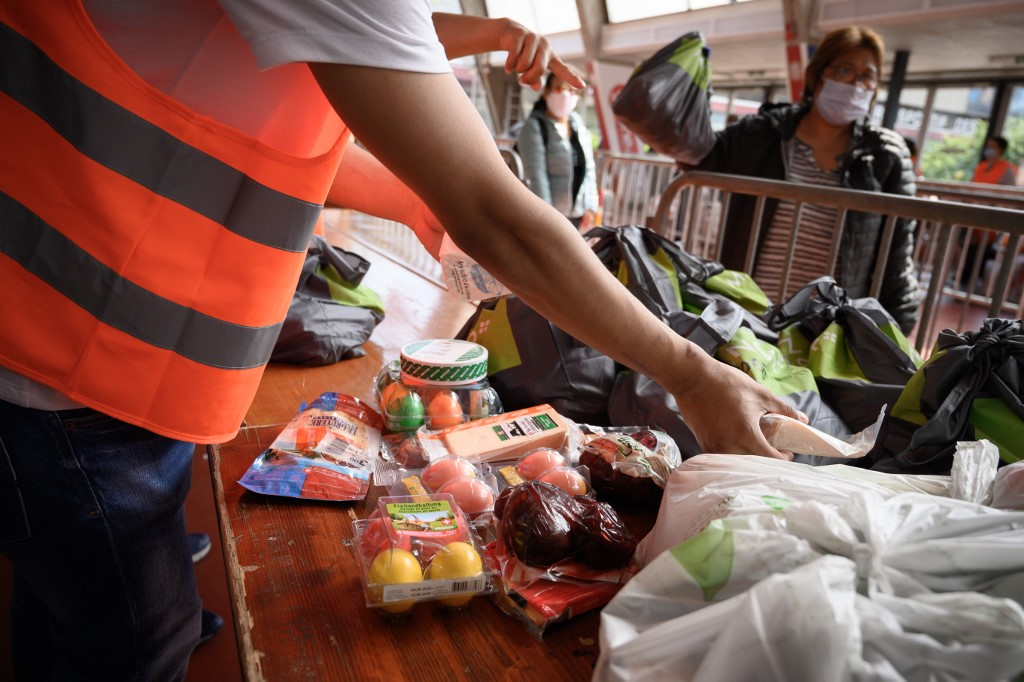 Volunteers hands out food bags at a free distribution point for the people in need on May 9, 2020, in Geneva, as the COVID-19 pandemic casts a spotlight on the usually invisible poor people of Geneva, one of the world's most expensive cities. (Photo by Fabrice COFFRINI / AFP)