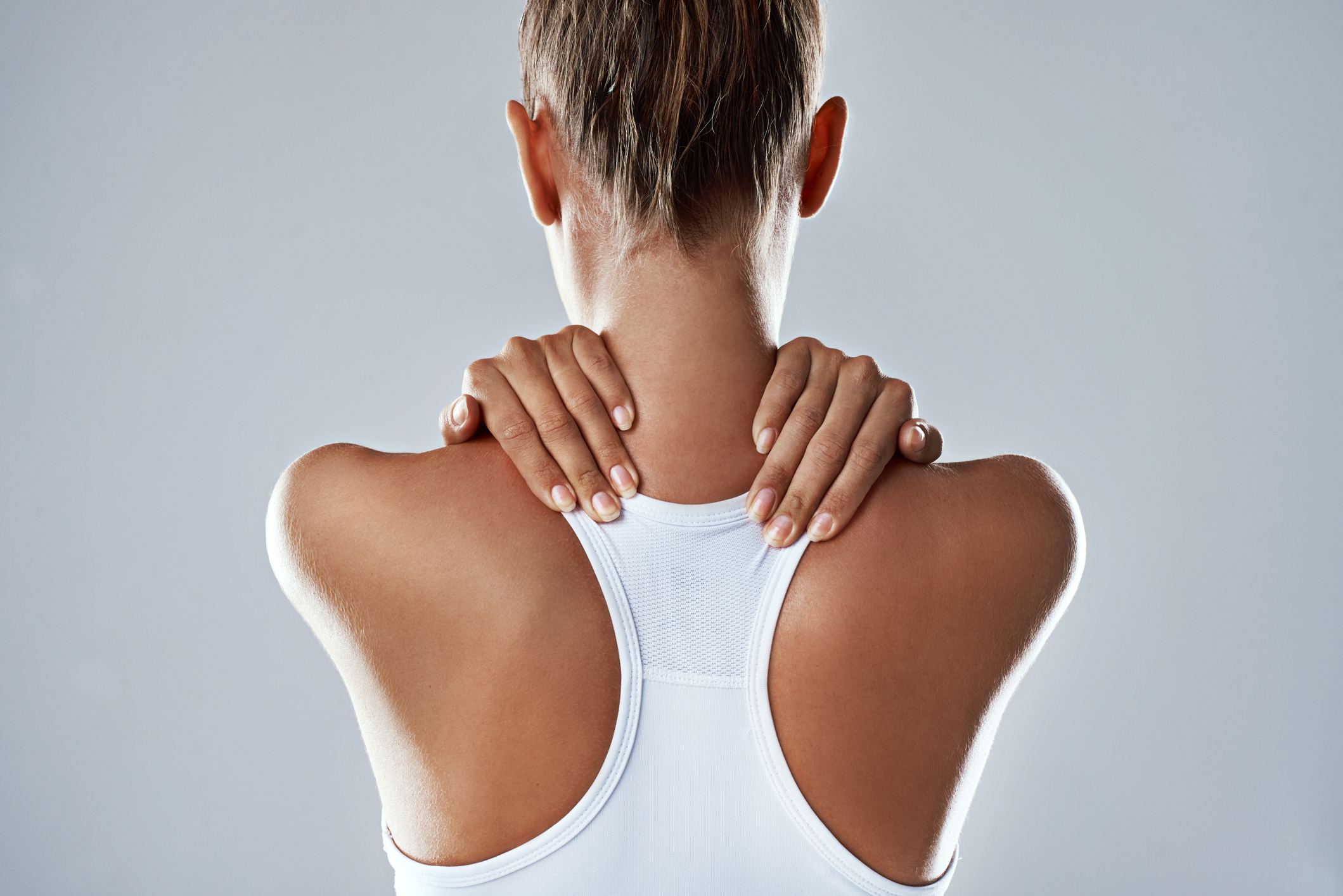 Studio shot of an athletic young woman holding her neck in pain against a grey background