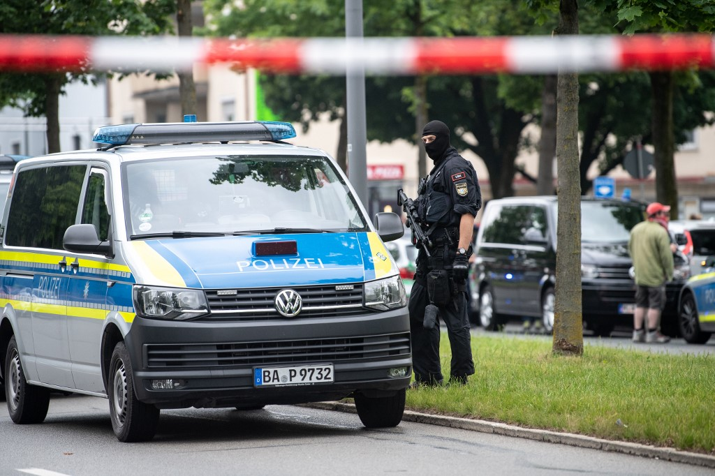 10 June 2020, Bavaria, Munich: A policeman with a machine pistol is standing near the spot where a vehicle drove into a group of people in the afternoon. Three people were injured, whether by the collision with the car or by the subsequent beating, was initially unclear. Photo: Matthias Balk/dpa