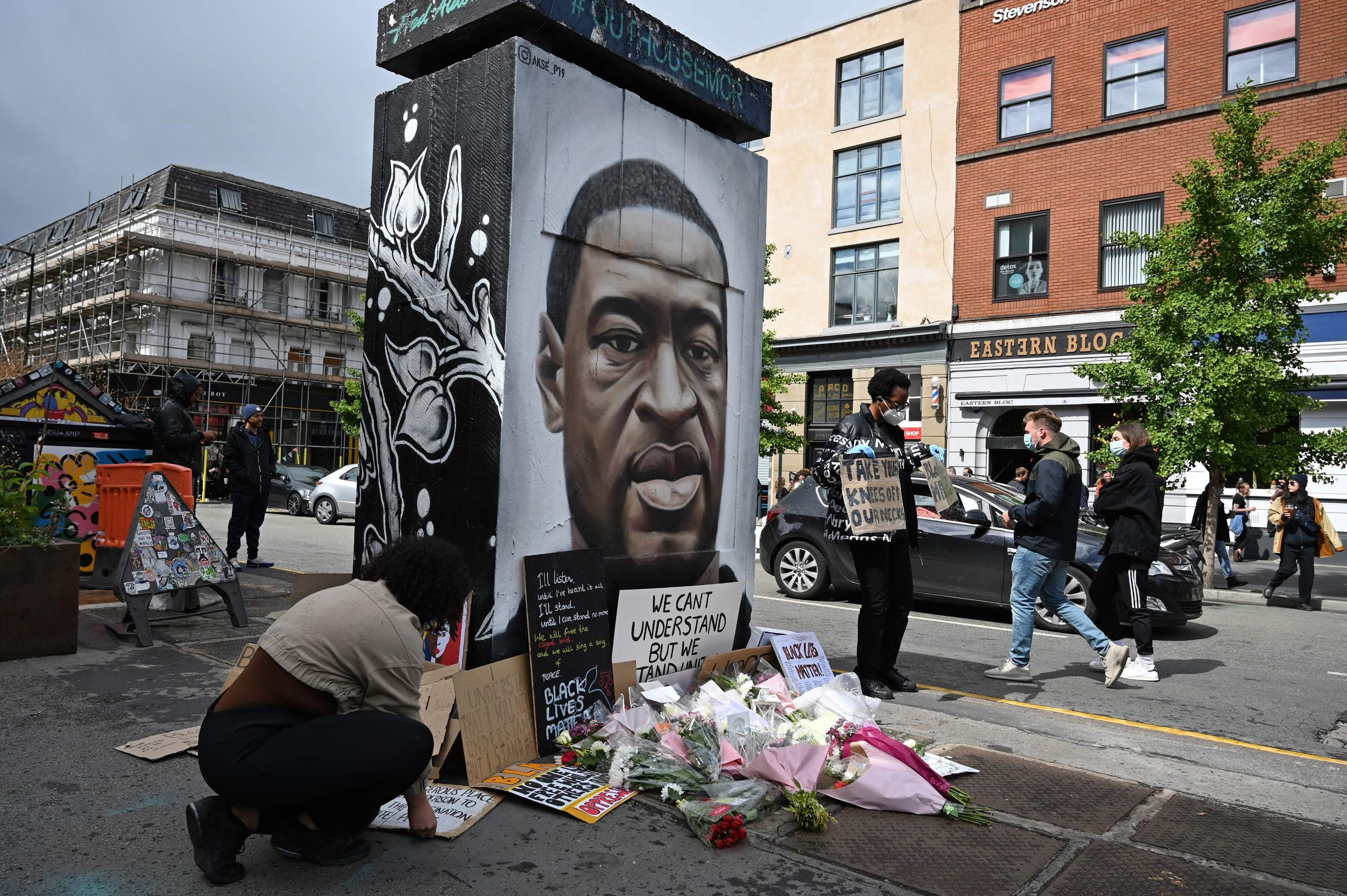 Protesters place their placards at the base of a mural of George Floyd, by street artist Akse, following a demonstration in Manchester, northern England, on June 6, 2020, to show solidarity with the Black Lives Matter movement in the wake of the killing of George Floyd, an unarmed black man who died after a police officer knelt on his neck in Minneapolis. - The United States braced Friday for massive weekend protests against racism and police brutality, as outrage soared over the latest law enforcement abuses against demonstrators that were caught on camera. With protests over last week's police killing of George Floyd, an unarmed black man, surging into a second weekend, President Donald Trump sparked fresh controversy by saying it was a