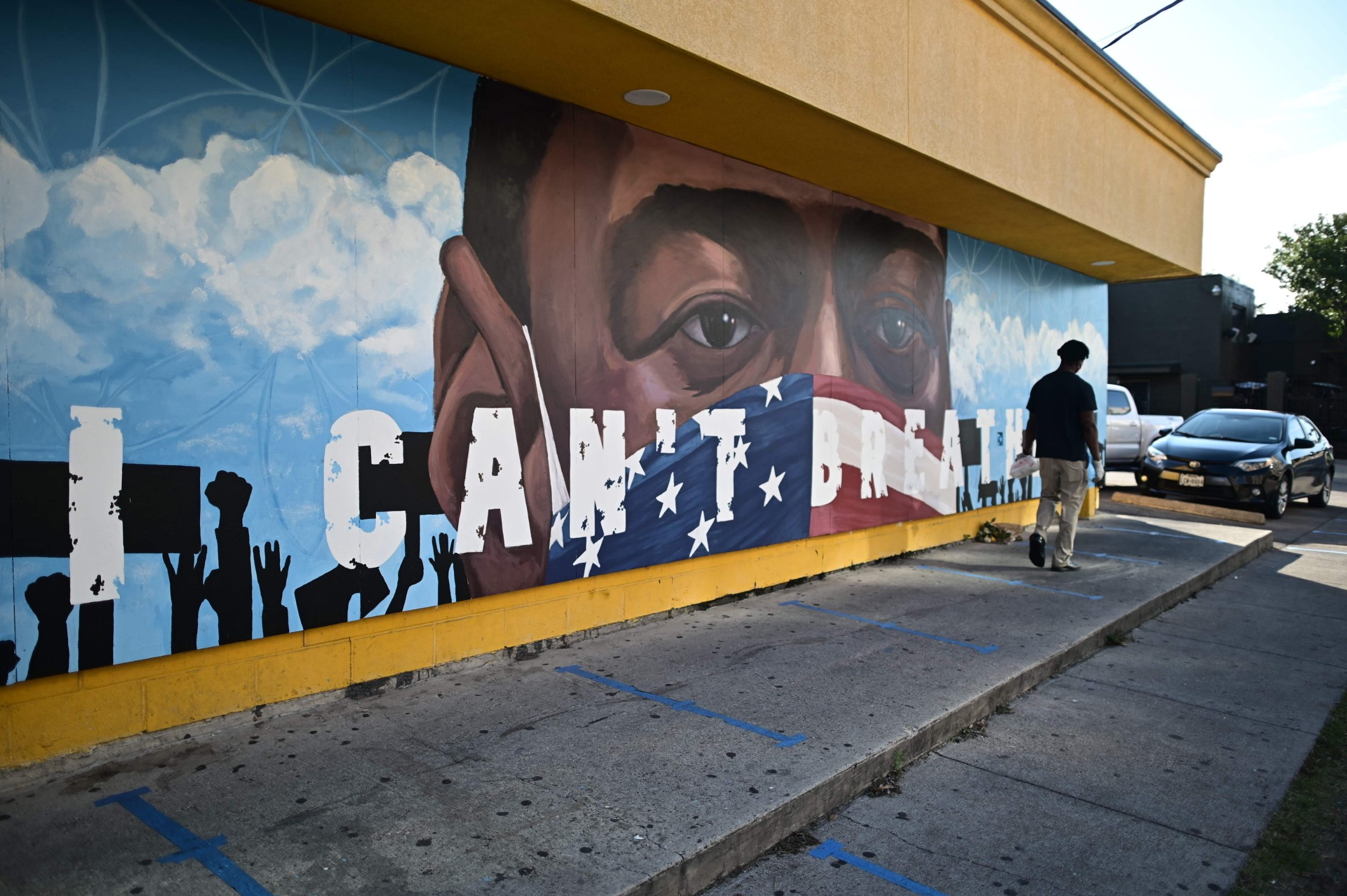 A person walks by a mural for George Floyd in Houston, Texas on June 8,2020. - Democrats vowed June 7, 2020 to press legislation to fight systemic racism in US law enforcement as the battle for change triggered by the police killing of George Floyd began shifting from the streets to the political sphere.Demonstrations continued across the nation Sunday -- including in Washington, New York and Winter Park, Florida -- as protesters began focusing their initial outrage over the death of the unarmed Floyd into demands for police reform and social justice. (Photo by Johannes EISELE / AFP)