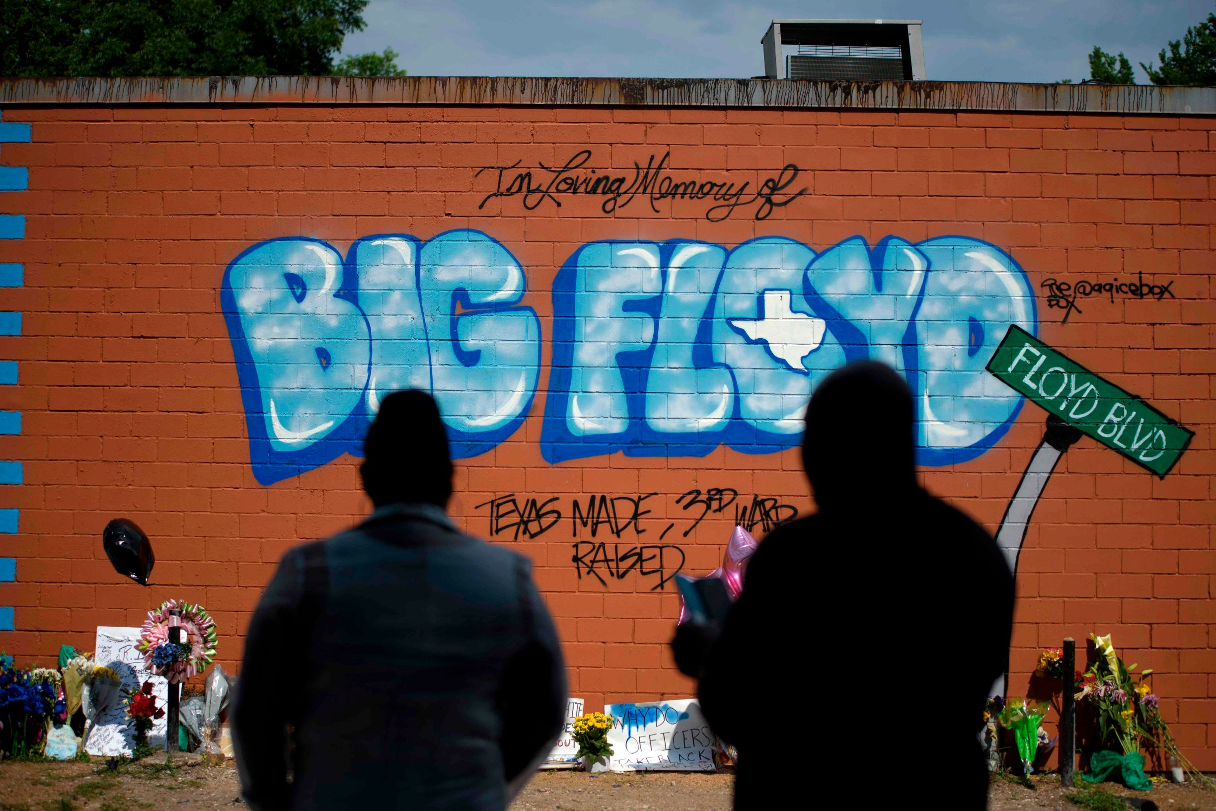 Visitors pay their respects to George Floyd at a mural in Houston, Texas on Monday, June 8, 2020. - Democrats vowed June 7, 2020 to press legislation to fight systemic racism in US law enforcement as the battle for change triggered by the police killing of George Floyd began shifting from the streets to the political sphere.Demonstrations continued across the nation Sunday -- including in Washington, New York and Winter Park, Florida -- as protesters began focusing their initial outrage over the death of the unarmed Floyd into demands for police reform and social justice. (Photo by Mark Felix / AFP)