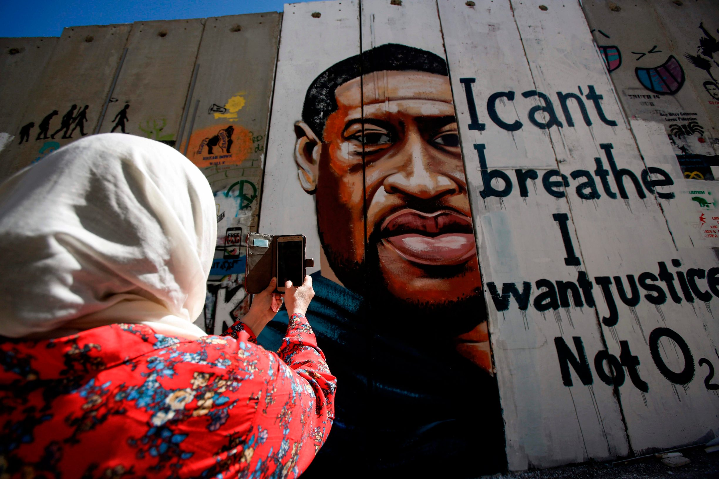 A woman uses her phone to photograph a mural showing the face of George Floyd, an unarmed black man who died after a white policeman knelt on his neck during an arrest in the US, painted on a section of Israel's controversial separation barrier in the city of Bethlehem in the occupied West Bank on June 10, 2020, with text reading
