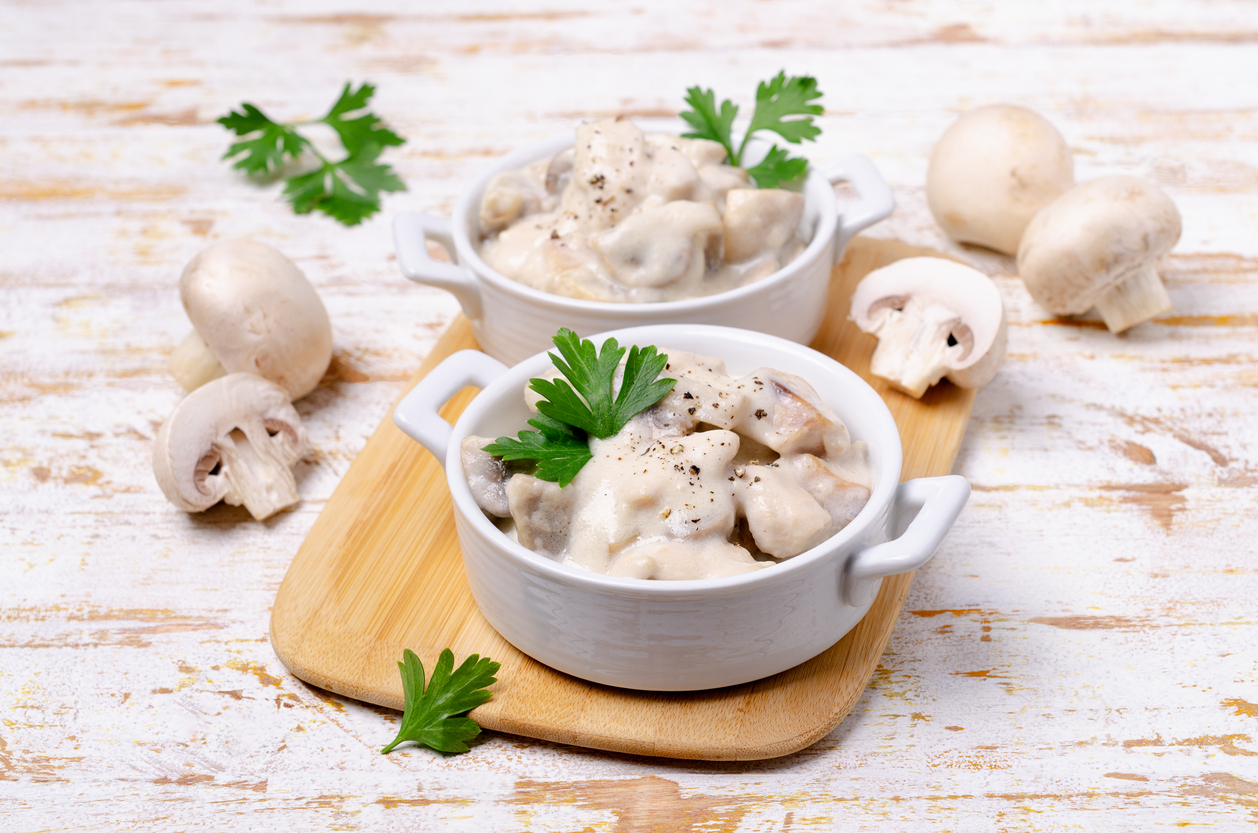 Slices of mushrooms and meat with white sauce on wooden background. Selective focus.