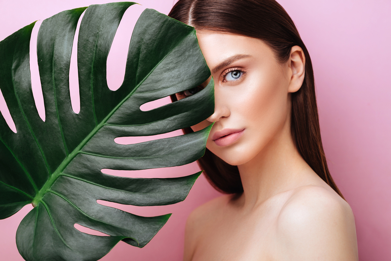 Beauty Woman with natural green palm leaf Portrait, model girl with perfect makeup, natural eyeshadows. Brunette Beautiful Fashion Model Girl Face. Skin care. Perfect Skin. On pink Background