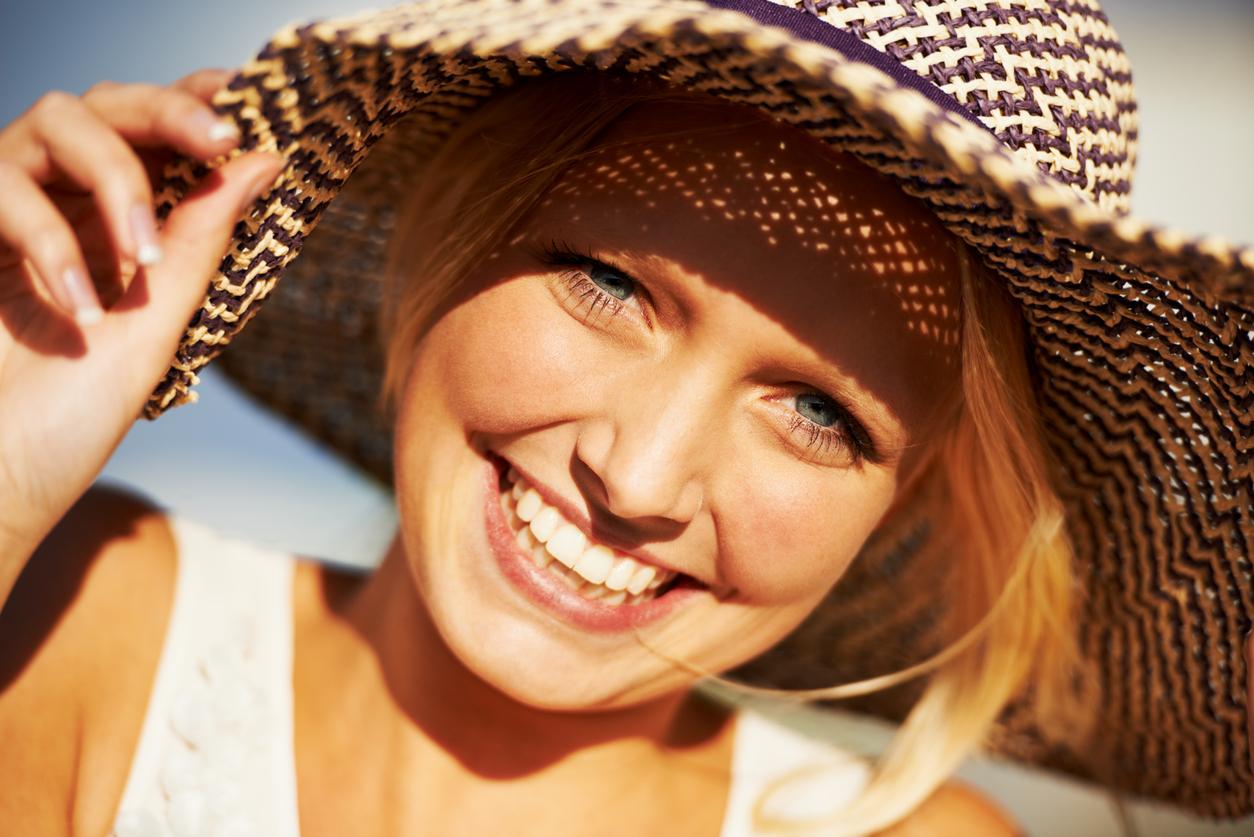 Closeup portrait of a beautiful blonde woman wearing a straw hat