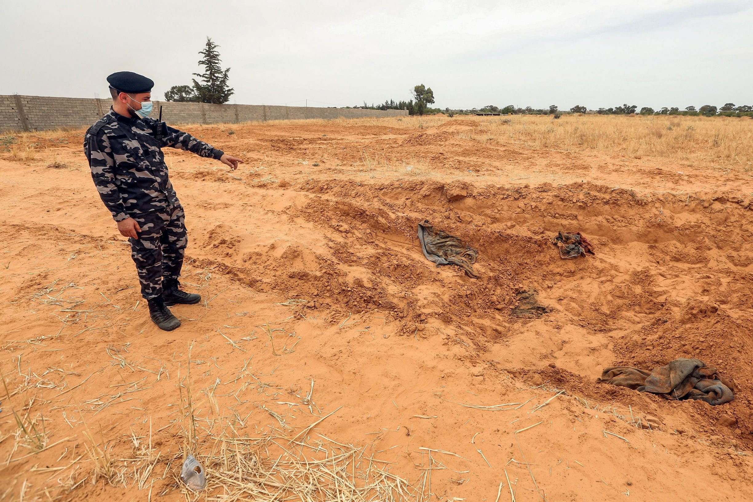A member of security forces affiliated with the Libyan Government of National Accord (GNA)'s Interior Ministry stands at the reported site of a mass grave in the town of Tarhuna, about 65 kilometres southeast of the capital Tripoli on June 11, 2020. - The United Nations mission to Libya on June 11 voiced