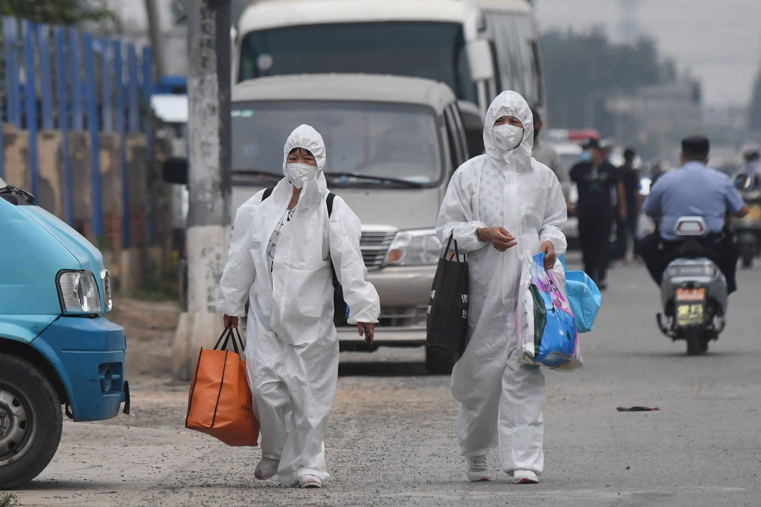 TOPSHOT - Two women wear protective suits as they walk on a street near the closed Xinfadi market in Beijing on June 13, 2020. - Eleven residential estates in south Beijing have been locked down due to a fresh cluster of coronavirus cases linked to the Xinfadi meat market, officials said on June 13. (Photo by GREG BAKER / AFP)