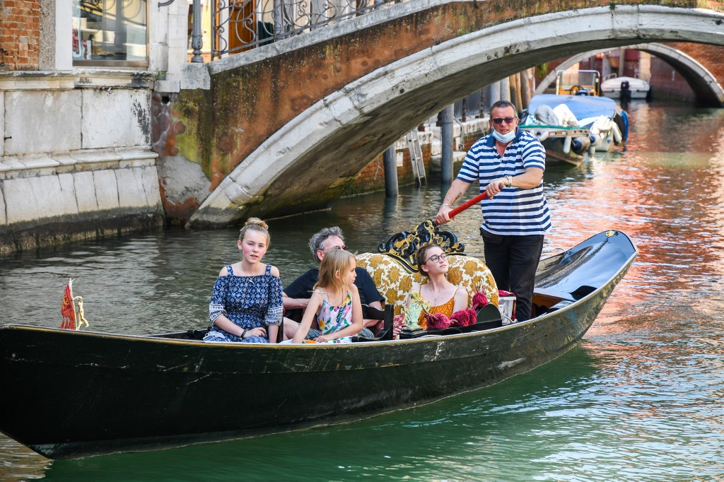 A gondolier goes with customers for a gondola ride on a canal in Venice on June 12, 2020 as the country eases its lockdown aimed at curbing the spread of the COVID-19 infection, caused by the novel coronavirus. (Photo by ANDREA PATTARO / AFP)