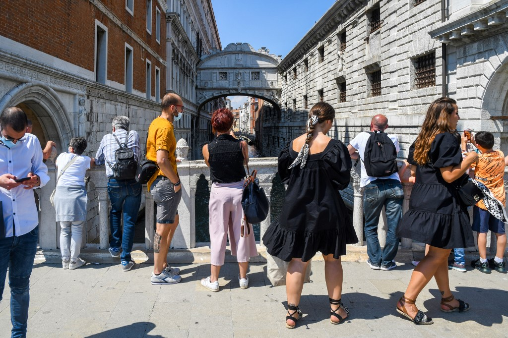 People view the Bridge of Sighs (Ponte dei Sospiri) on June 12, 2020 in Venice as the country eases its lockdown aimed at curbing the spread of the COVID-19 infection, caused by the novel coronavirus. (Photo by ANDREA PATTARO / AFP)