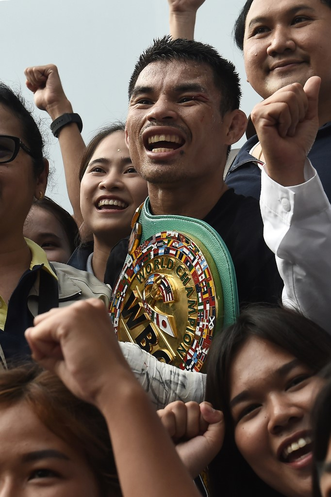 Undefeated Thai boxer Wanheng Menayothin wears his WBC title belt while surrounded by fans after defeating Panamanian challenger Leroy Estrada to win his 50th straight victory on May 2, 2018 in Nakhon Ratchasima . - The 32-year-old Thai nicknamed the