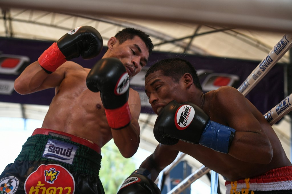 Thai boxer Wanheng Menayothin (L) lands a blow against Panamanian challenger Leroy Estrada (R) to win his 50th straight victory on May 2, 2018 in Nakhon Ratchasima and retain his WBC title. - The 32-year-old Thai nicknamed the