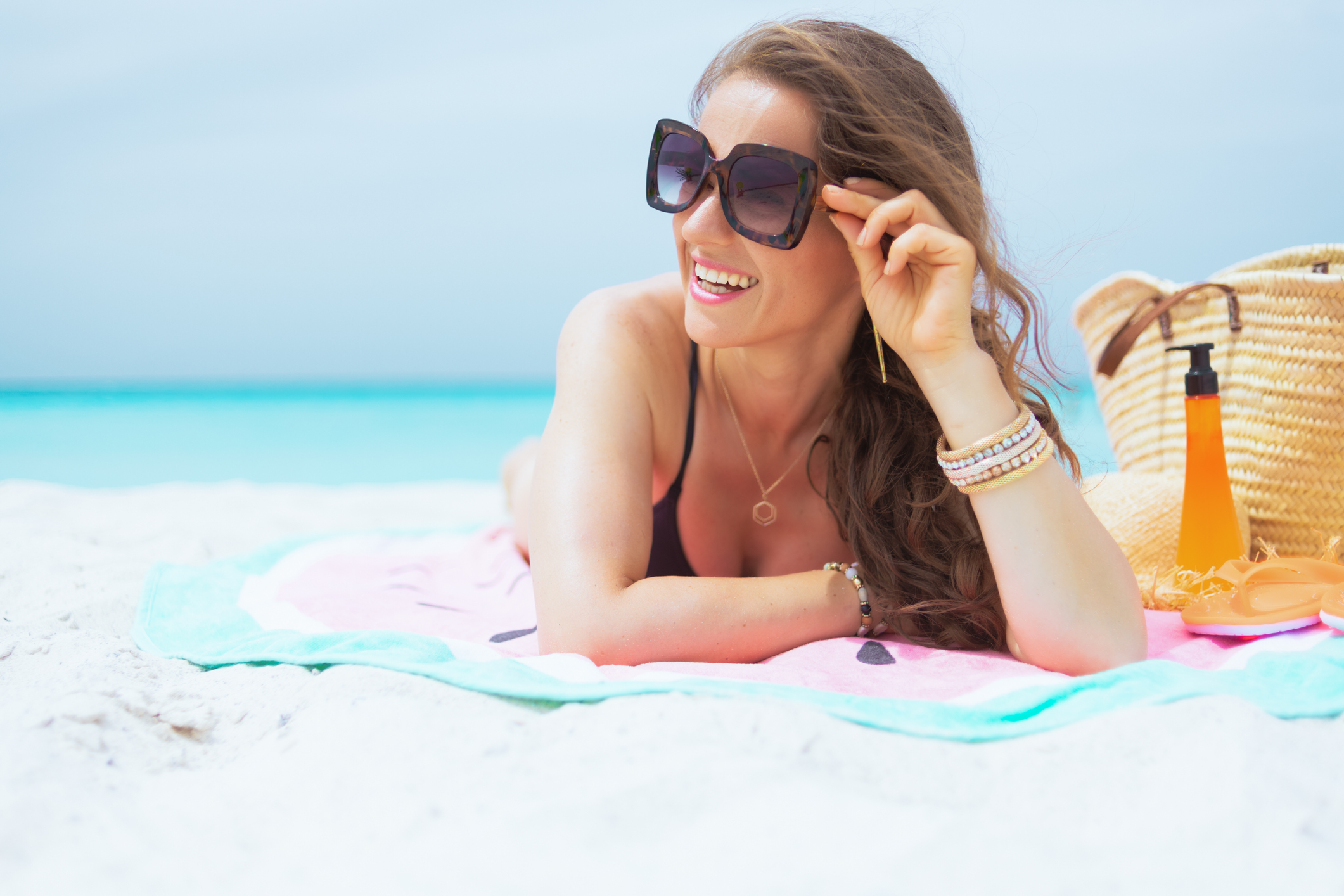 smiling stylish 40 year old woman in sunglasses and with long curly hair in elegant black bathing suit on a white beach looking into the distance and sun tanning.