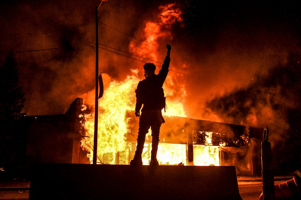 A protester reacts standing in front of a burning building set on fire during a demonstration in Minneapolis, Minnesota, on May 29, 2020, over the death of George Floyd, a black man who died after a white policeman kneeled on his neck for several minutes. - Violent protests erupted across the United States late on May 29 over the death of a handcuffed black man in police custody, with murder charges laid against the arresting Minneapolis officer failing to quell seething anger. (Photo by Chandan KHANNA / AFP)