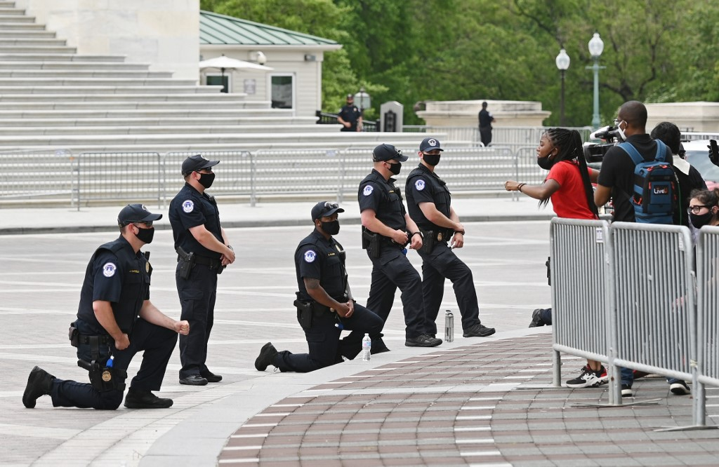 A protesters demonstrating against the death of George Floyd talks to Capitol Police on the East Front of the US Capitol on June 3, 2020, in Washington, DC. - The United States has erupted into days and nights of protests, violence, and looting, following the death of George Floyd after he was detained and held down by a knee to his neck, dying shortly after. (Photo by MANDEL NGAN / AFP)
