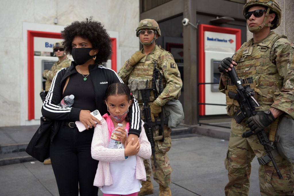 A mother and her daughter stand in front of a row of Army National Guard during a demonstration over the death of George Floyd in Los Angeles on June 2, 2020. - Anti-racism protests have put several US cities under curfew to suppress rioting, following the death of George Floyd in police custody. (Photo by Agustin PAULLIER / AFP)