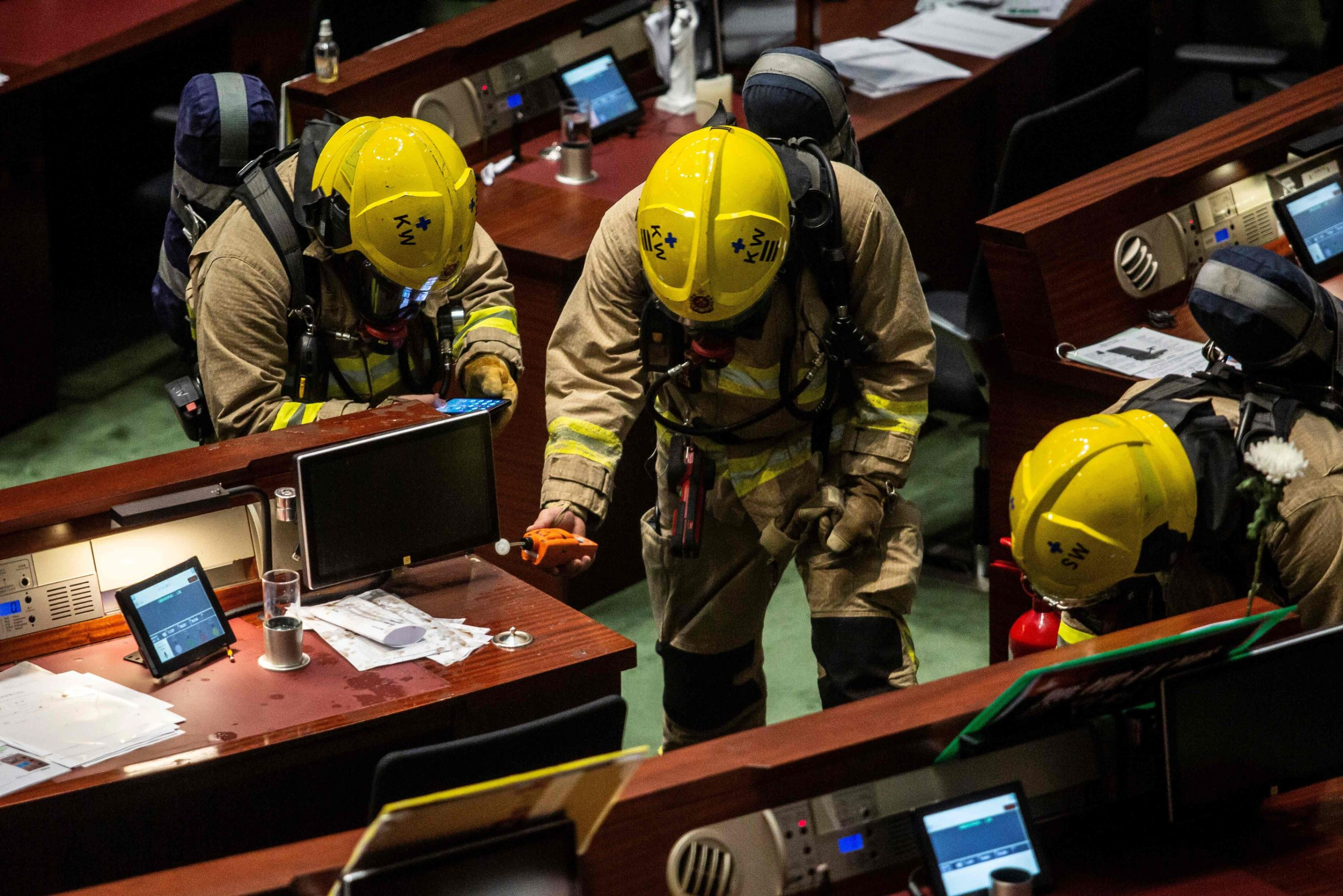 Members of the fire brigade perform tests in the main chamber of the Legislative Council after pan-democrat lawmakers hurled an odorous liquid during the third reading of the national anthem bill in Hong Kong on June 4, 2020, ahead of a vote over a law that bans insulting China's national anthem. (Photo by ISAAC LAWRENCE / AFP)
