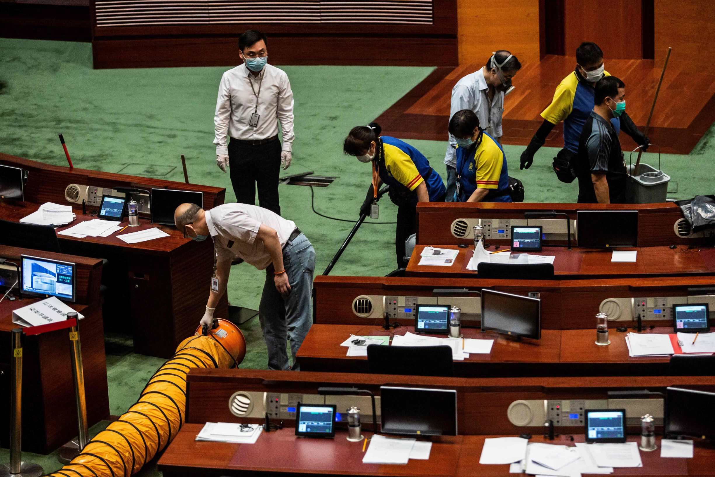 A ventilation tube (L) is set up as workers (top R) clean a section in the main chamber of the Legislative Council after pan-democrat lawmakers hurled an odorous liquid during the third reading of the national anthem bill in Hong Kong on June 4, 2020, ahead of a vote over a law that bans insulting China's national anthem. (Photo by ISAAC LAWRENCE / AFP)