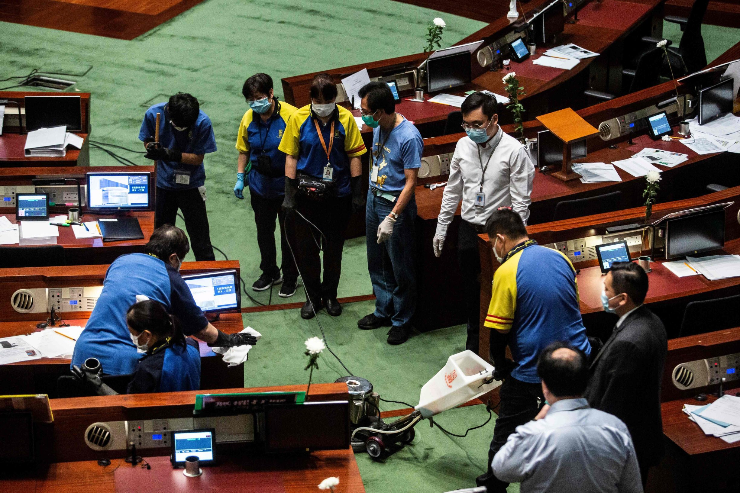 Workers clean a section in the main chamber of the Legislative Council after pan-democrat lawmakers hurled an odorous liquid during the third reading of the national anthem bill in Hong Kong on June 4, 2020, ahead of a vote over a law that bans insulting China's national anthem. (Photo by ISAAC LAWRENCE / AFP)