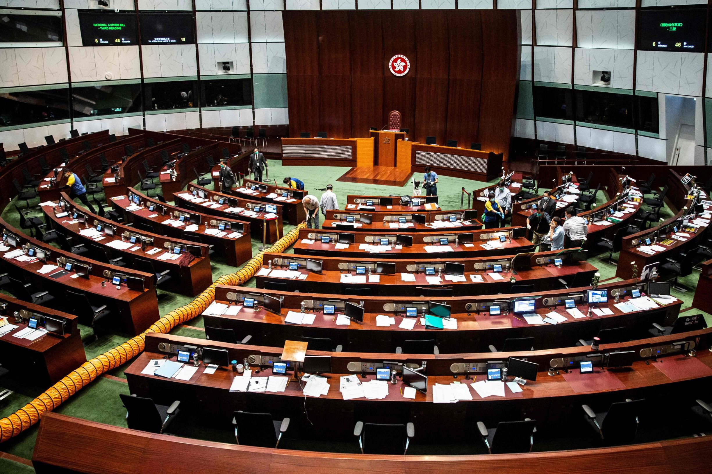 A ventilation tube (L) is set up as workers (R) clean a section in the main chamber of the Legislative Council after pan-democrat lawmakers hurled an odorous liquid during the third reading of the national anthem bill in Hong Kong on June 4, 2020, ahead of a vote over a law that bans insulting China's national anthem. (Photo by ISAAC LAWRENCE / AFP)