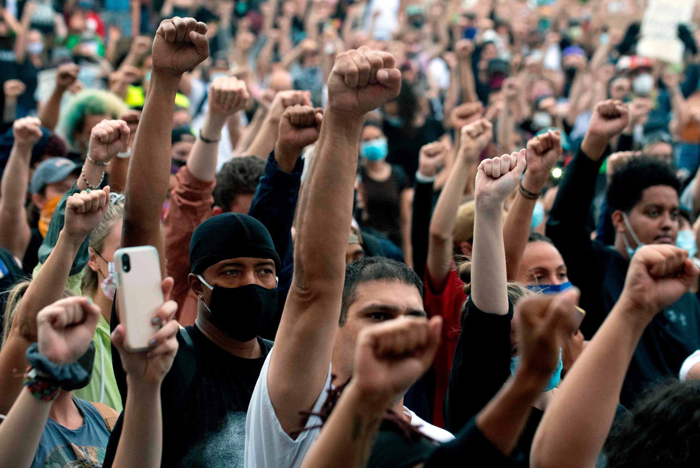 Demonstrators raise their fists in a sign of solidarity while protesting the death of George Floyd, an unarmed black man who died while while being arrested and pinned to the ground by the knee of a Minneapolis police officer, at the  Colorado State Capital in Denver, Colorado on June 3, 2020. - US protesters welcomed new charges brought Wednesday against Minneapolis officers in the killing of African American man George Floyd -- but thousands still marched in cities across the country for a ninth straight night, chanting against racism and police brutality. (Photo by Jason Connolly / AFP)