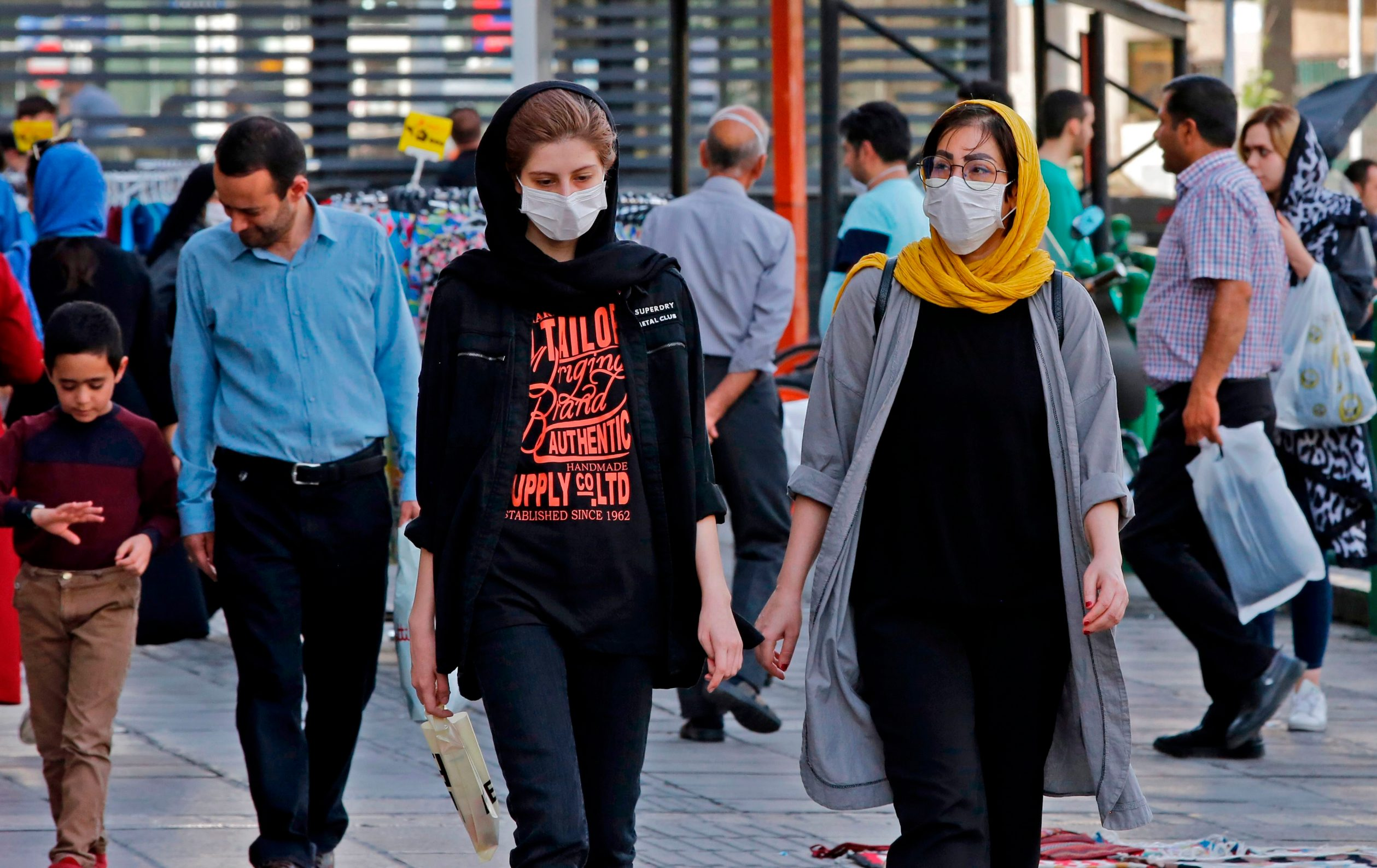 Iranians, some wearing face masks, walk along a street in the capital Tehran on June 3, 2020, amid the novel coronavirus pandemic crisis. - The spread of novel coronavirus has accelerated again this month in Iran which today officially confirmed over 3,000 new cases for a third consecutive day. (Photo by - / AFP)