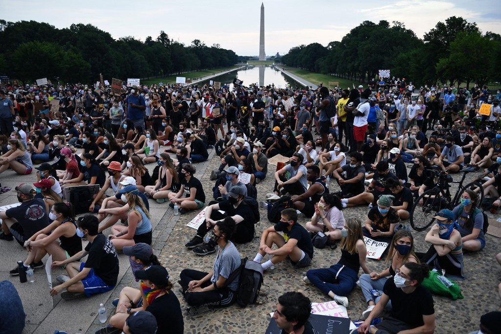 People attend a demonstration at the Lincoln Memorial Reflecting Pool, protesting the death of George Floyd, who died in police custody in Minneapolis, in , DC, on June 4, 2020. - On May 25, 2020, Floyd, a 46-year-old black man suspected of passing a counterfeit  bill, died in Minneapolis after Derek Chauvin, a white police officer, pressed his knee to Floyd's neck for almost nine minutes. (Photo by Brendan Smialowski / AFP)