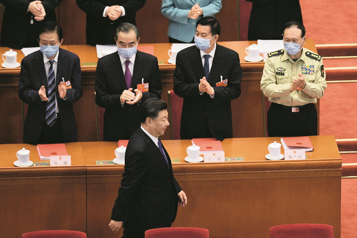 TOPSHOT - Chinese President Xi Jinping is applauded by, from left, State Councilor Xiao Jie, Foreign Minister Wang YiState Councilor Wang Yong, and Defence Minister Wei Fenghe, as he arrives for the closing session of the National People's Congress at the Great Hall of the People in Beijing on May 28, 2020. - China's rubber-stamp parliament endorsed plans May 28 to impose a national security law on Hong Kong that critics say will destroy the city's autonomy. (Photo by NICOLAS ASFOURI / AFP)