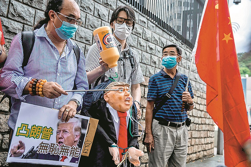 A pro-China activist holds an effigy of US President Donald Trump during a protest outside the US consulate in Hong Kong on May 30, 2020, in response to US President Donald Trump saying on May 29 he would strip several of Hong Kong's special privileges with the United States and bar some Chinese students from US universities in anger over Beijing's bid to exert control in the financial hub. (Photo by ISAAC LAWRENCE / AFP)