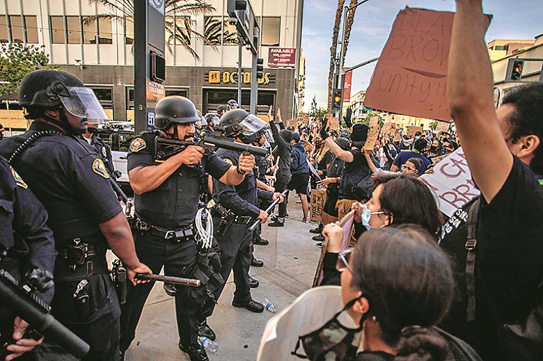 Demonstrators try to block Police officers while they take position aiming towards the crowd in Downtown Long Beach on May 31, 2020 during a protest against the death of George Floyd, an unarmed black man who died while while being arrested and pinned to the ground by the knee of a Minneapolis police officer. - Protests sweeping the United States over the death of George Floyd reverberated on the other side of the globe Monday when thousands marched in solidarity on the streets of New Zealand. (Photo by Apu GOMES / AFP)