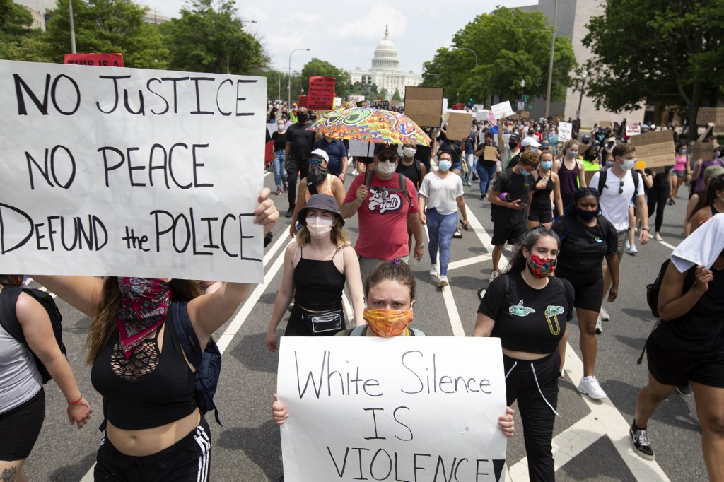 Demonstrators hold placards as they march to the White House during a peaceful protest against police brutality and racism, on June 6, 2020 in Washington, DC. - Demonstrations are being held across the US following the death of George Floyd on May 25, 2020, while being arrested in Minneapolis, Minnesota. (Photo by Jose Luis Magana / AFP)