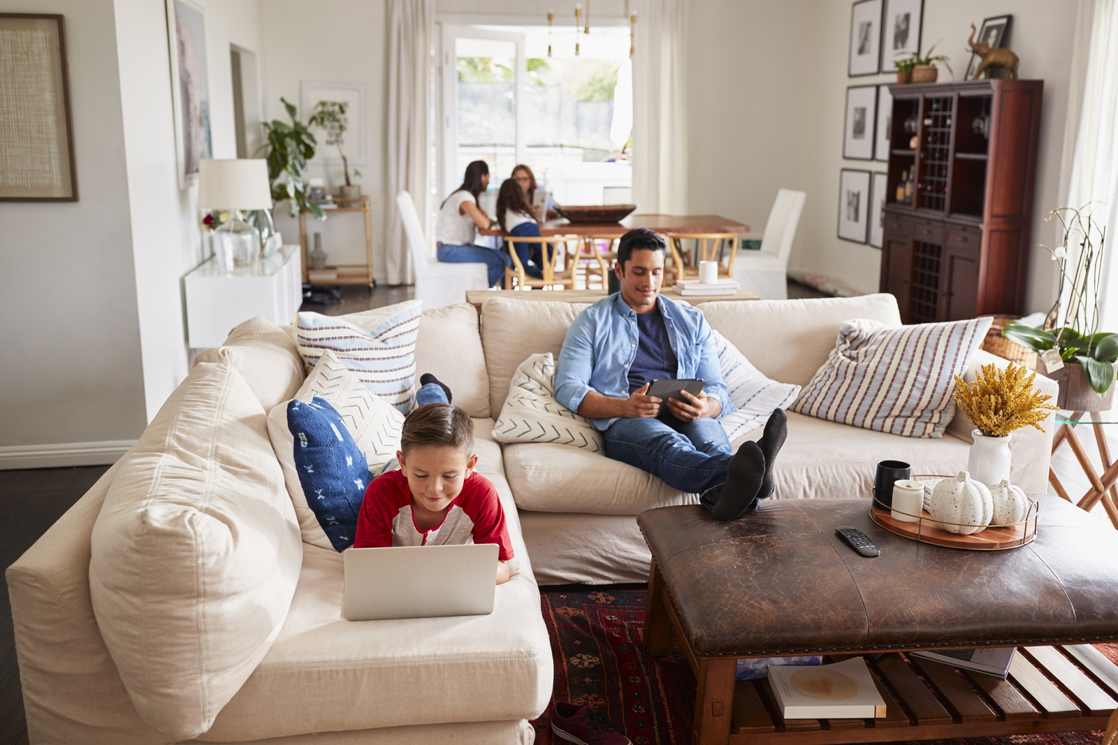 Pre-teen boy lying on sofa using laptop, dad using tablet, mum, sister and grandma in the background